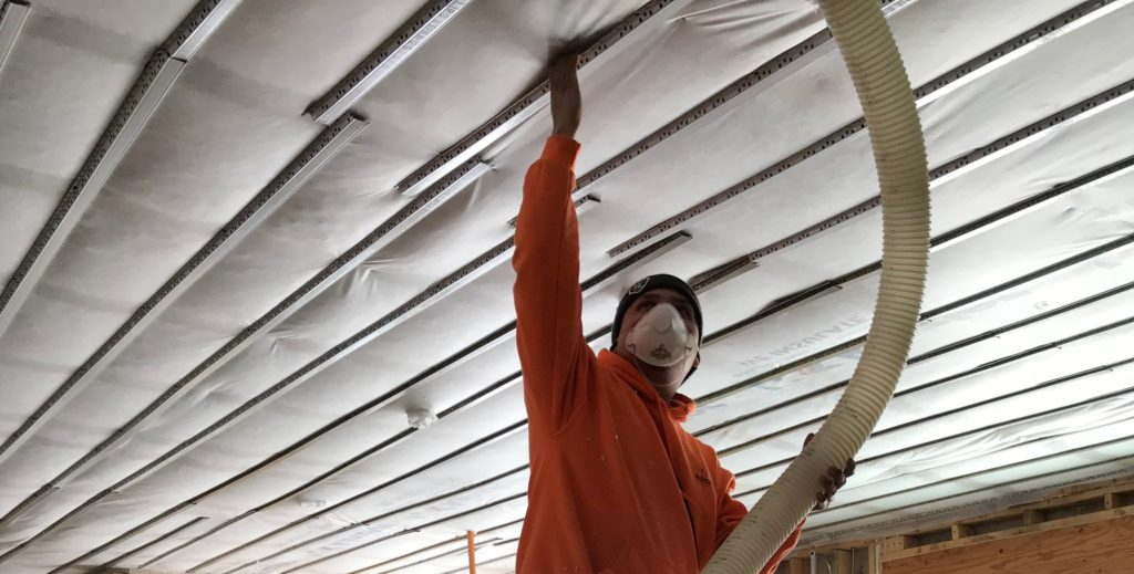 A Kinzler insulation installer blows in insulation in a ceiling.